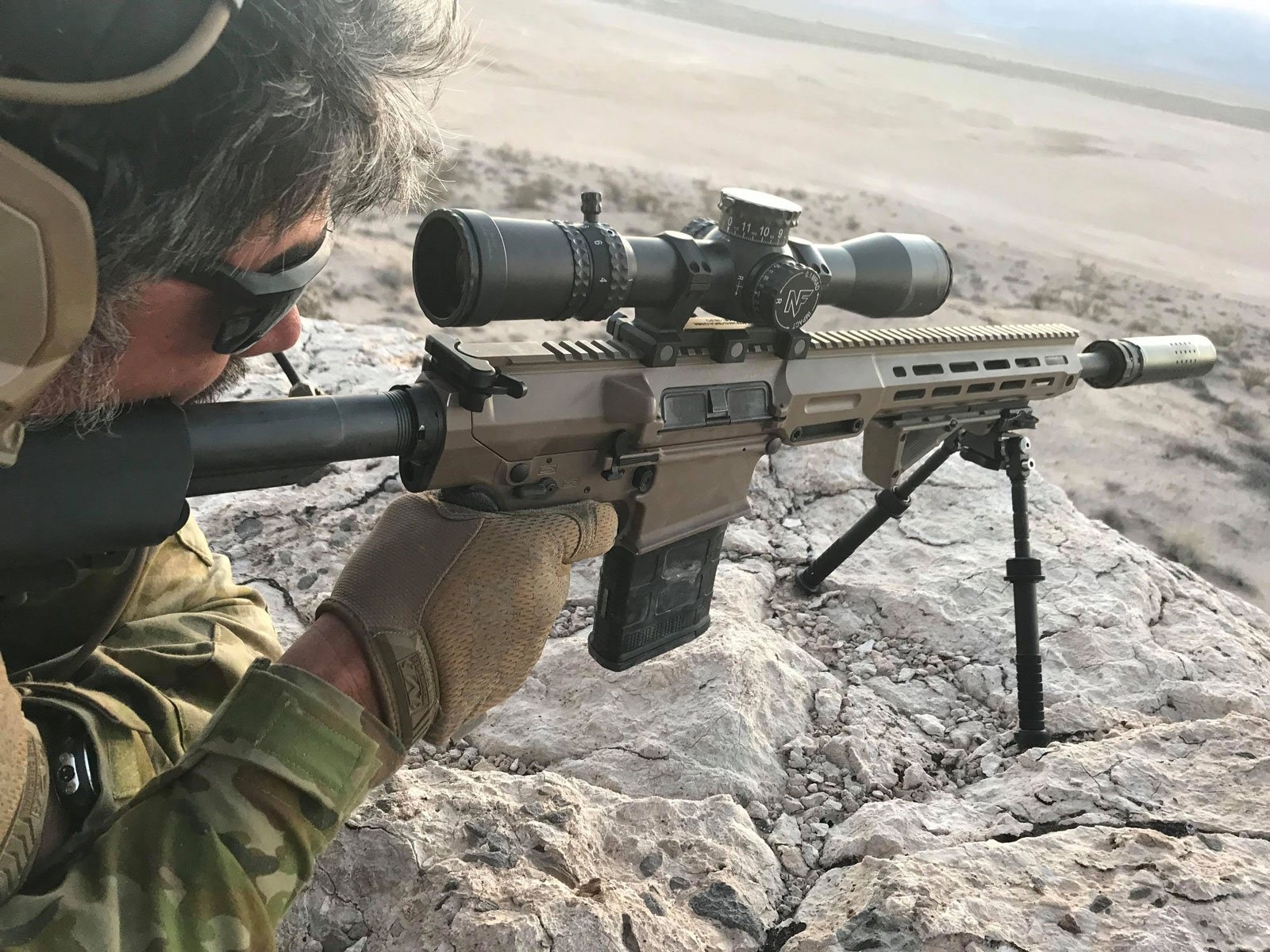 Captain (ret.) Reece Dewar OAM checks the sights on his rifle